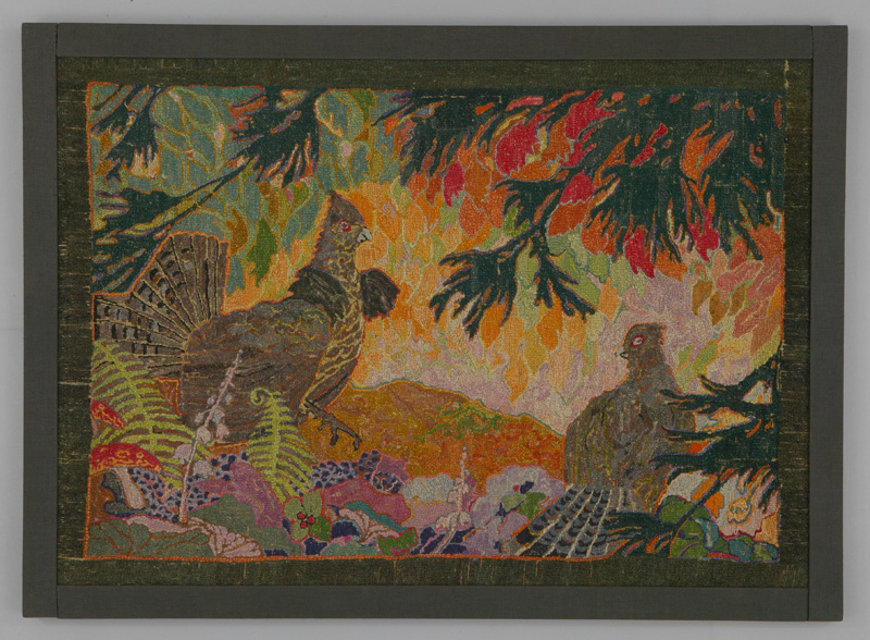 A rug hooking depicting a scene of two birds in a lush forest scene, brightly coloured orange, red and yellow plants and trees surrounding them.