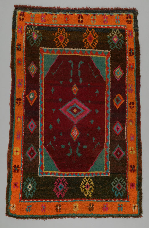 A rectangular floor rug decorated with geometric shapes and hues of orange, brown and turquoise created using a knotted pile technique.