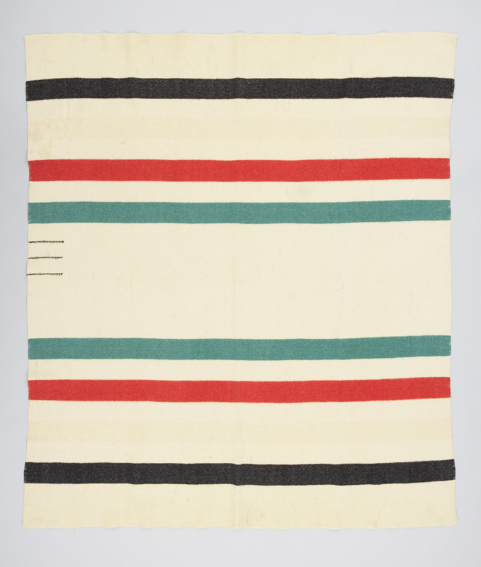A white rectangular woven wool blanket with a series of thin horizontal stripes in red, green and black. Three small strips at one edge indicate the size.