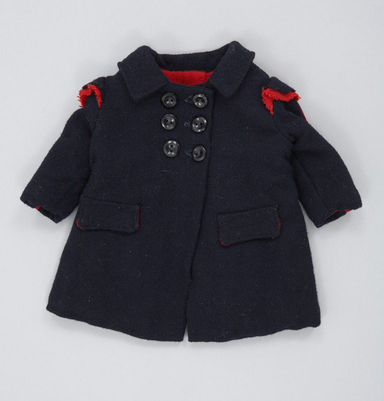 A small handmade doll's coat made of dark blue wool, lined with red wool, and embellished on the sleeves and shoulders with red piping.