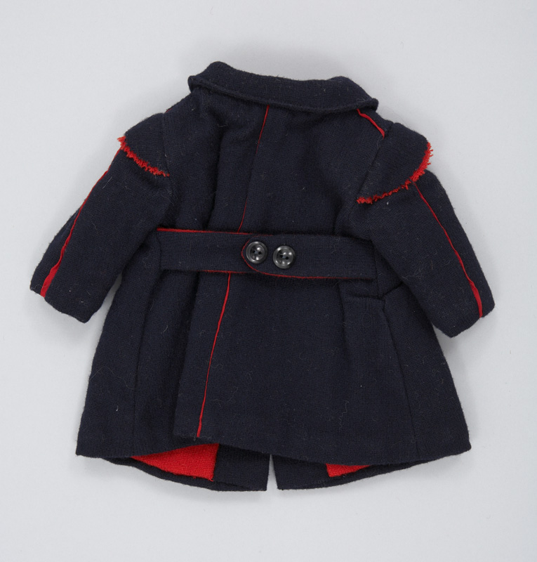 Rear view of a handmade doll's coat made of dark blue wool, lined with red wool and embellished on the sleeves and shoulders with red piping.