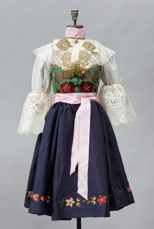 Girl's outfit, a silk skirt with woolen apron embroidered at the hem, pink silk ribbons, white cotton blouse with lace collar and a brocade vest.