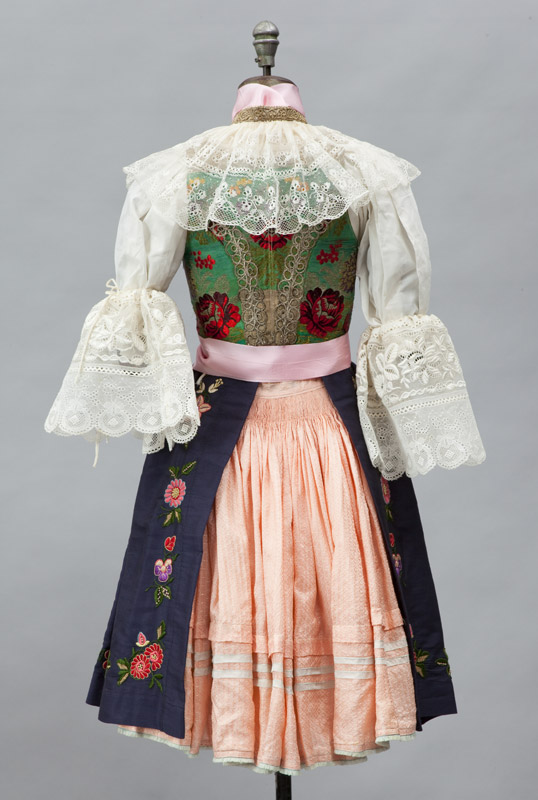 Rear view of girl's outfit, a silk skirt with woolen apron embroidered at the hem, pink silk ribbons, white cotton blouse and a brocade vest.