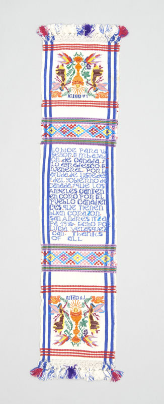 A white rectangular woven textile panel with blue borders and red highlights depicting angels and a communion chalice bearing a dedication of thanks.