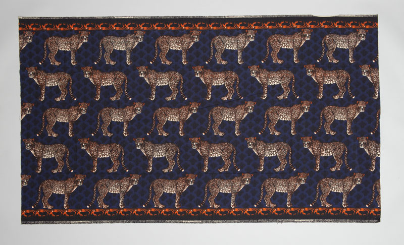 Rectangular cloth printed with repeating pattern of a standing yellow leopard on dark blue background, typically worn wrapped atop the head by women in Mozambique.