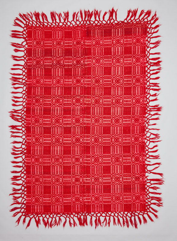 A rectangular sheep's wool coverlet with fringe and a stylized geometric pattern in red, a popular colour in Macedonian textile work.