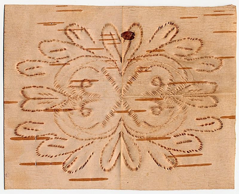 A piece of birch bark with detailed floral designs bit into it by artist Angelique Merasty.