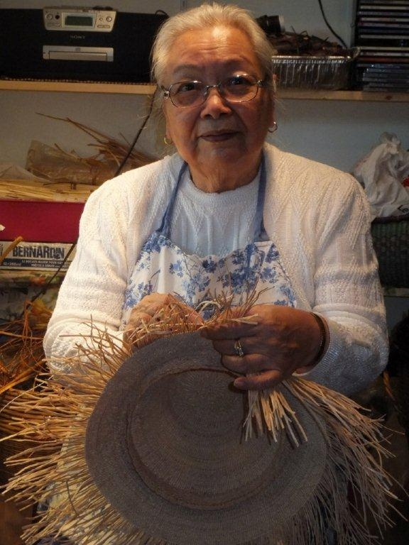 Rena Point Bolton smiles for the camera while weaving a cedar hat in her studio.