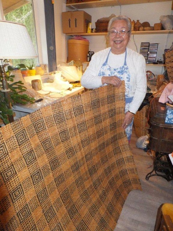 Rena Point Bolton holds up part of a large geometrically patterned black and natural cedar mat.