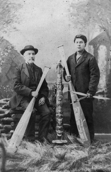 Posed portrait of Johnny Kit Elswa and James Swan standing beside a small totem pole, holding wooden oars, 1883.